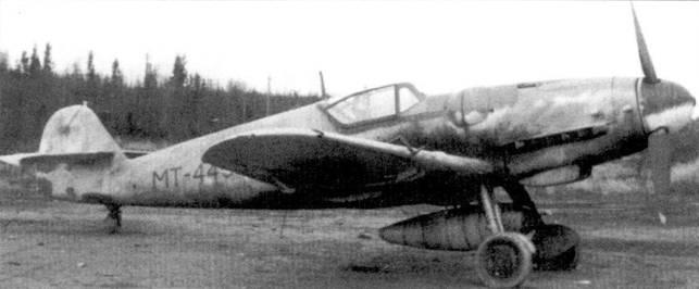 Истребитель Bf 109G (бортовой код «МТ-445») из 3/HLeLv-34, снимок второй половины сентября 1944г. Желтая идентификационная полоса Восточного фронта вокруг фюзеляжа уже закрашена. Самолет «МТ-445» — один из 14 «пятиточечных» Bf. 109G-6/R-6 полученных финнами из Германии. 20 июня 1944г. истребитель закрепили за стафф- сержантом Клаусом «Сантту» Алакоски. Алакоски сбил на нем восемь советских самолетов, правда крыльевые пушки с «ганбота» сняли практически сразу же после прибытия истребителя в Финляндию. Алакоски одержал 26 побед, выполнил 239 боевых вылетов.