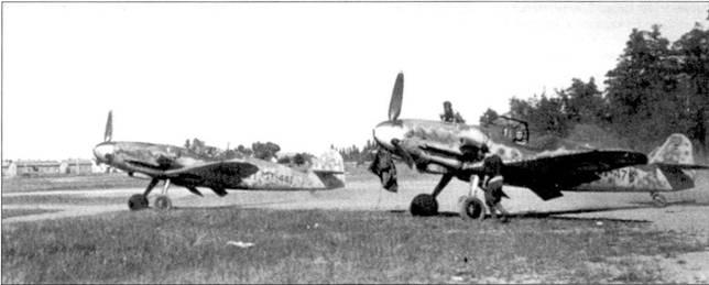 Истребители Bf. 109G из 3/Н LeLv-24 сфотографированы на аэродроме Лаппиинранта 3 июля 1944г.; на переднем плане — самолет с бортовым кодом «МТ-476». Чаще всего на нем лепки мастер-сержант Нильс Катаяйнен (35,5 побед). 5 июля 1944г. Катаяйнен был ранен в воздушном бою с истребителями Як-9. Ас сумел посадить разбитый мессершмитт, после чего несколько месяцев пропел в госпиталях. На заднем плане — истребитель с бортовым кодом «XI Т-441», на котором восемь из десяти своих побед одержал I-й лейтенант Ахти Лайтинен. 29 июня 1944г. Лайтинен был сбит на <a href='https://arsenal-info.ru/b/book/2753724368/7' target='_self'>мессершмитте</a> «МТ-439» (на этой машине чаще всего лепки Ханс Винд) и ноши в плен после удачного прыжка с парашютом.