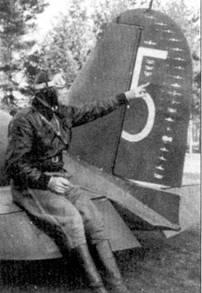 Летчик 1/LeLv-26 уоррент-офицер Ойва Туоминен поясняет победную символику, украшающую руль направления его Фиата G.50 (бортовой код «FA-26»), снимок 22 октября 1942г.