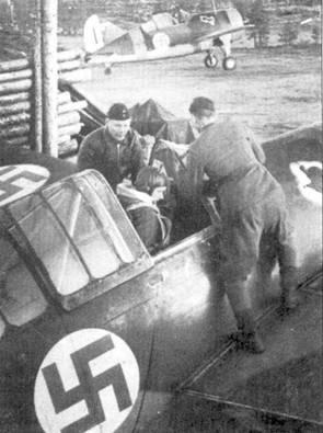 Механики помогают командиру 4/LeLv-24 1- му лейтенанту Никке Тюрюнену занять место в кабине Брюстера с бортовым кодом «BW-380», аэродром Рюмпютти, начало октября 1942г. На заднем плане выруливает на старт Брюстер с бортовым кодом «В W- 377», в кабине которого находится сержант Тапио Ярви. Тюрюнен к моменту гибели 2 мая 1943г. имел на своем счету 11 побед. Ярви остался в живых, он одержал в воздушных боях 28,5 побед.