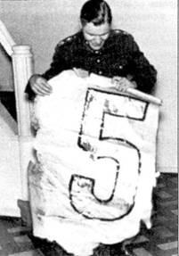В офицерском клубе аэродрома Нммола Сарванто демонстрирует кусок обшивки руля направления с одного из сбитых им в историческом бою бомбардировщиков ДБ-3, снимок сделан 7 января 1940г. Чтобы сбить шесть ДБ-3М из 6-го ДБАП Сарванто пришлось израсходовать 2000 патронов к пулеметам — весь боекомплект.