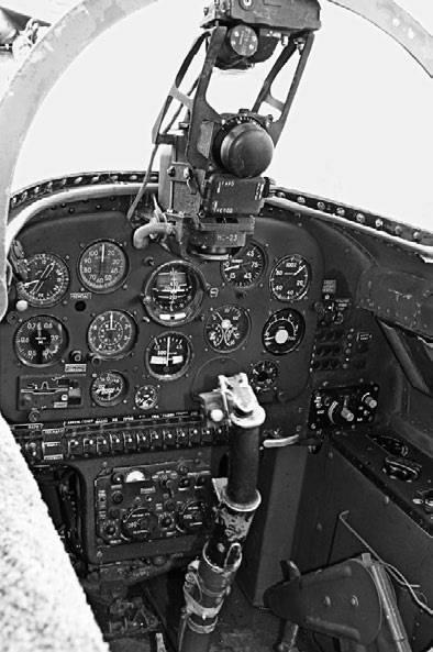 Фрагмент кабины курсанта самолета Як-30. Перед лобовым стеклом фонаря виден стрелковый прицел АСП-3Н с фотопулеметом, а на ручке управления самолетом – боевые кнопки для стрельбы из пушки НС-23 и <a href='https://arsenal-info.ru/b/book/2633435995/28' target='_self'>реактивными снарядами</a>
