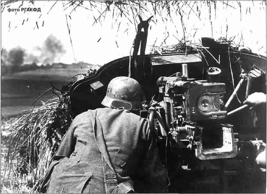 Немецкое противотанковое орудие РаК 40 ведёт огонь по атакующим советским танкам. На щите орудия закреплены ножницы для резки колючей проволоки. Август 1943г.