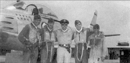 Полковник Джэймс Джонсон, как и свой предшественник в должности командира 4-о авиакрыла полковник Тинг, считался одним us лучших лидеров истребительной авиации ВВС США. На снимке — «двойные» асы, сбившие в воздушных боях над Ялу 54 МиГа. Слева направо: капитан Лонни Мур (10 побед), подполковник Вермонт Гаррисон (10 побед), командир крыла полковник Джэймс Джонсон 10побед), капитан Ральф Парр (девять МиГ-15 и один Ил-2), майор Джэймс Джабара (15 побед, все — МиГи). На заднем плане — истребитель F- 86F полковника Джонсона. Несмотря на то что, на борту самолета отметки о девяти победах. Джонсон сбил на нем всего один-два самолета.