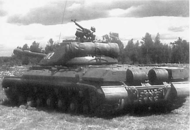 36.Танк Т-10А, вид сзади слева (кадр учебного кинофильма). Хорошо видны топливные баки и укладка БДШ.