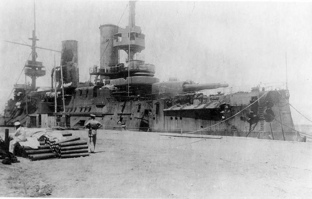 """""""Цесаревич"""" в Цындао. На первом плане видны сложенные гильзы от 152-мм патронов. Их охраняют русский и германские матросы. На ограждении носового мостика видна пробоина от 152-мм снаряда которым был убит штурман лейтенант Драгишич-Никшич."""