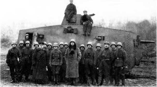 Танк A7V №506 из 1-го «штурмового отделения» под командованием лейтенанта Фосса на полигоне близ Бёвиля во время совместного обучения с подразделениями 5-го штурмового батальона, начало февраля 1918г. Пятый слева, в шинели и фуражке — капитан Йозеф Фольмер. Танк с корпусом «Рёхлинг» первого заказа, «козловой» установкой орудия и ранним вариантом бронирования кожухов пулеметов, в монохромной окраске. Большинство членов экипажа — в рабочих комбинезонах и стальных шлемах, за исключением механиков и водителя, использующих защитные «шоферские» шлемы.