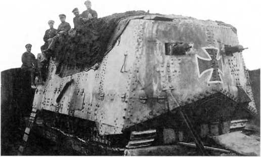 Танк A7V погружен на железнодорожную платформу (вид с кормы). Рубка управления сложена, на танк наброшена маскировочная сеть.