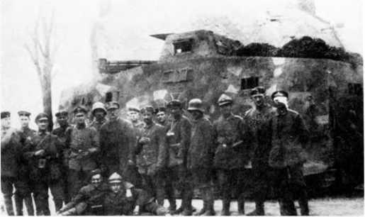 Экипаж танка A7V из состава 1-го «штурмового отделения». Танк — с корпусом «Рёхлинг», пестрой камуфляжной окраской и «железными крестами». Обратим внимание на сочетание элементов экипировки экипажа — можно увидеть обычную полевую форму с поясным ремнем и без него, солдатские бескозырки, стальные шлемы и защитные «шоферские» шлемы. Офицер — в плаще.