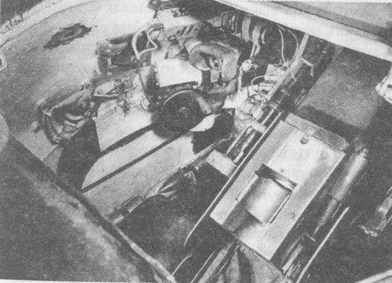 Вид внутрь башни танка Т-34 через башенный люк. Слева от казённика пушки Ф-34 хорошо различима трубка телескопического прицела ТМФД-7, выше её – налобник и окуляр перископического прицела ПТ-4-7 и маховик поворотного механизма башни. Над последним размещён аппарат №1 ТПУ командира танка. Левее и ниже аппарата ТПУ видна рамка бортового смотрового прибора, пользоваться которым, судя по снимку, командиру танка было весьма затруднительно