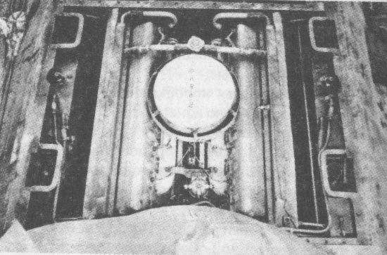 Вид на двигатель танка Т-34 со стороны башни. За «блином» воздухоочистителя виден заливной тройник с паровоздушным клапаном, предназначенный для заливки воды в систему охлаждения. По бортам, между шахтами подвески, видны масляные баки