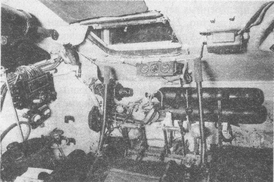 Отделение управления танка Т-34. Место механика-водителя. Чёрный цилиндр слева вверху – уравновешивающий механизм крышки люка. Справа от люка, над баллонами со сжатым воздухом – аппарат ТПУ