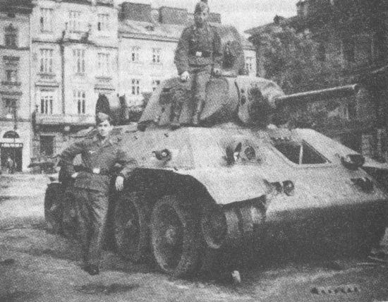 Немецкие солдаты осматривают танк Т-34 с пушкой Л-11, потерявший гусеницу и оставленный экипажем на улице Львова. Июнь 1941 года