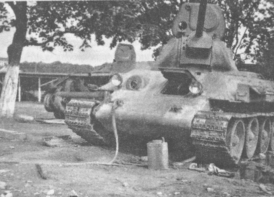 Неисправные танки Т-34, брошенные в ремонтных мастерских. На откинутой крышке башенного люка хорошо видны заглушка на месте прибора кругового обзора и откинутая крышка лючка для флажковой сигнализации. 1941 год