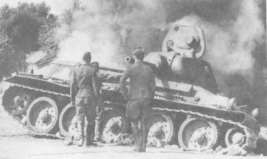 Немецкие солдаты осматривают подбитый танк Т-34. Лето 1941 года. Эта машина оснащена литой башней, что было редкостью – большая часть «тридцатьчетвёрок» довоенного выпуска, тем более ранних, с пушкой Л-11, имела сварные башни
