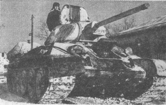 Танк Т-34 проходит через освобождённую деревню. Январь 1942 года