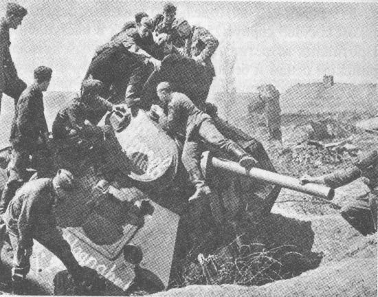 Немецкие солдаты осматривают подбитый под Харьковом советский танк Т-34. Весна 1942 года