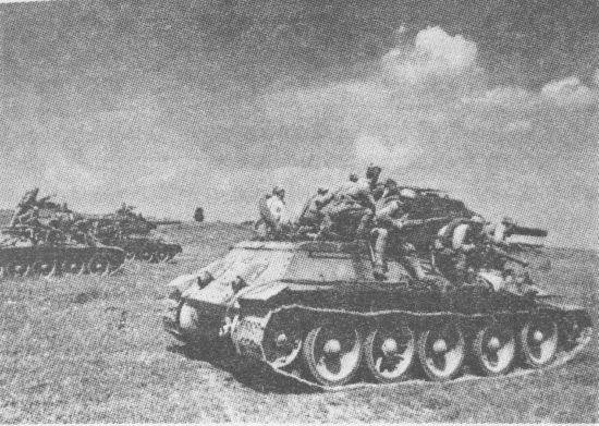 Танк Т-34 с десантом автоматчиков устремляется в атаку. Курская дуга, июль 1943 года. Из-за сильной раскачки удержаться на броне Т-34 в движении было довольно трудно, поэтому пехотинцы часто привязывали себя ремнями к десантным поручням