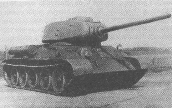 Один из первых танков Т-34-85 с пушкой Д-5Т на полигоне в Кубинке. Хорошо видны типичные лишь для этой модификации маска пушки, антенный ввод на правом борту корпуса, поручни на лобовой броне, расположение сильно смещённых вперёд командирской башенки и дополнительного топливного бака, а также выполненные из прутков рымы для демонтажа башни