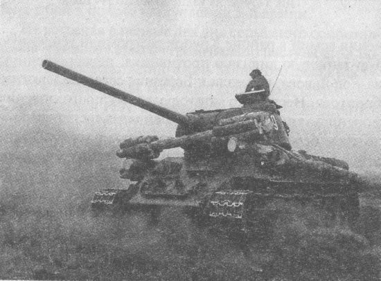 Танк Т-34-85 с самодельной деревянной фашиной. Обращает на себя внимание приоткрытый люк механика-водителя. С приоткрытым люком ходили даже в атаку, так как рассмотреть что-либо через приборы наблюдения было практически невозможно