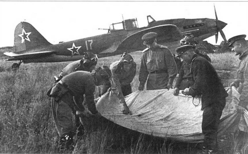 В перерывах между боями идет интенсивная боевая учеба. Молодые летчики рассматривают пробоины в конусе после учебных воздушных стрельб.