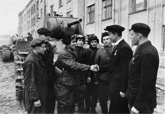 Работники Кировского завода в Ленинграде передают готовые танки КВ-1 экипажам. Сентябрь 1941 года. Машины оснащены дополнительными прямоугольными топливными баками, установленными на надгусеничных полках (АСКМ).