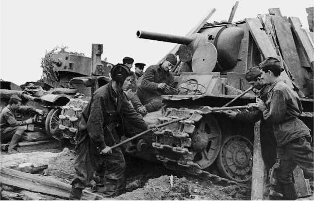 Ремонт танков после боя. Ленинградский фронт, 5 августа 1942 года. За замаскированным досками КВ-1 виден танк Т-26 с цилиндрической башней (АСКМ).