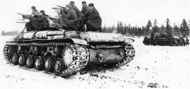 Отработка взаимодействия танков КВ-1 с десантом пехоты. Западный фронт, январь 1942 года. На фото машина выпуска осени 1941 года с дополнительными топливными баками и литыми усиленными катками с внутренней амортизацией (РГАКФД).