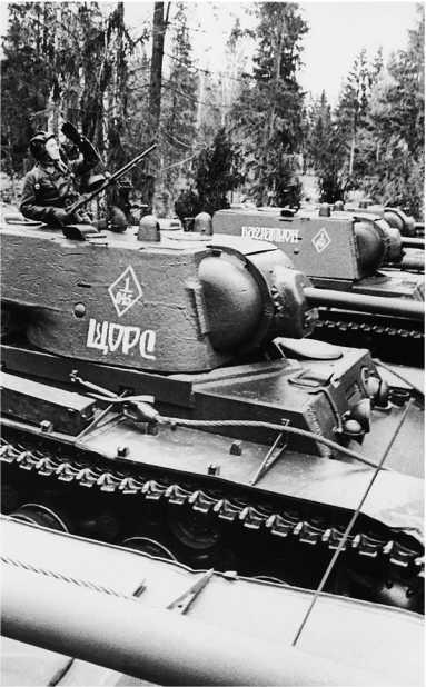 Танкист КВ-1 «Щорс» наблюдает за воздухом. Западный фронт, май 1942 года. На фото танки из 1 — го батальона (о чем свидетельствует цифра 1 в верхней части ромба) (РГАКФД).