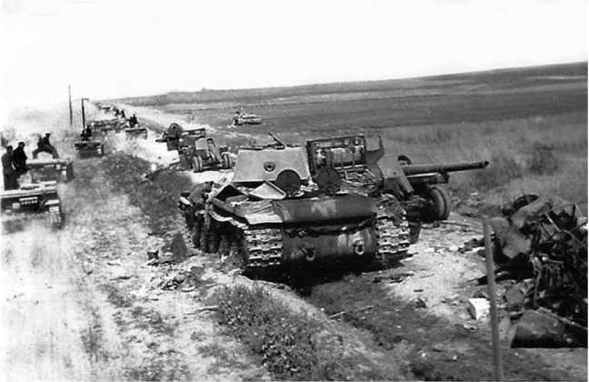 Подбитый или оставленный из-за отсутствия горючего КВ-1 2-й танковой дивизии 3-го мехкорпуса. Литва, июнь 1941 года. Рядом с танком стоят брошенные 152-мм гаубицы М-10, слева проходит колонна немецких танков. Впереди в поле виден еще один КВ (ЯМ).