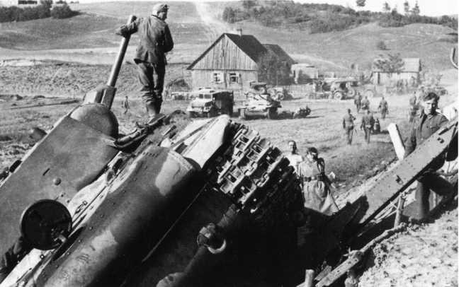 Немецкие солдаты осматривают КВ-1 (с пушкой Л-11) из состава 2-й танковой дивизии 3-го мехкорпуса. Литва, район Расейняя, июнь 1941 года. Машина вышла из строя или была подбита и съехала с дороги в кювет. На заднем плане виден немецкий полугусеничный тягач и подбитый танк Pz.II (АСКМ).