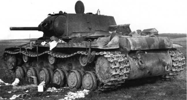 Подбитый в бою танк КВ-1 (с пушкой Л-11) 2-й танковой дивизии 3-го мехкорпуса. Литва, район Расейняя, июнь 1941 года. В маске пушки видна пробоина — судя по размерам от 88-мм зенитки или 105-мм пушки. Этот же танк виден в поле (на заднем плане) на одной из предыдущих фото (АСКМ).