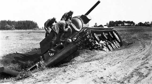 Еще один КВ-1 из состава 6-го мехкорпуса. Скорее всего, машина из-за поломки или неопытности механика-водителя съехала с дороги и застряла. Попытки вытащить (видны подложенные под гусеницу железнодорожные шпалы) ни к чему не привели, и танк был оставлен экипажем (АСКМ).