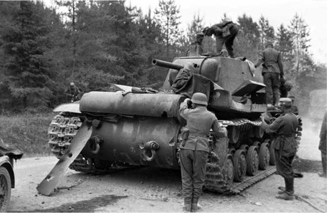 Немецкие солдаты осматривают подбитый КВ-1 из состава 32-й танковой дивизии 4-го мехкорпуса. Хорошо видны пробоины и следы снарядных попаданий в корме машины. Предположительно танк подбит в районе Яворова.