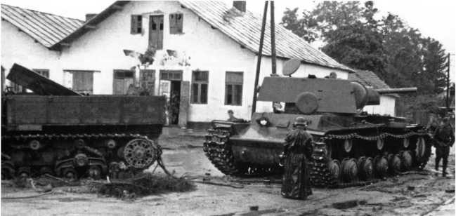 Танк КВ-1, буксируемый тягачом «Ворошиловец», на улице местечка Сасов (20 километров северо-восточнее Золочева). Июль 1941 года (АСКМ).