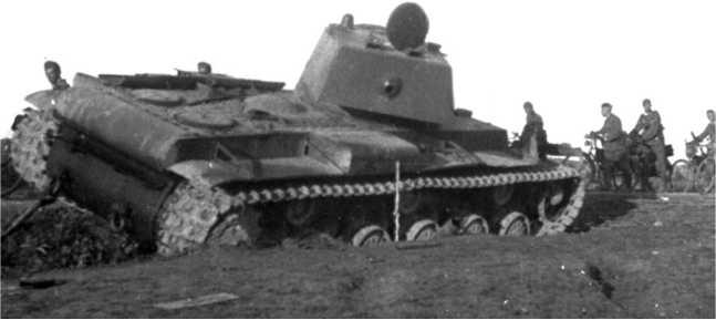 Вверху: второй КВ-1 из батальона ВАММ, подбитый под Дагдой 2 июля 1941 года. Как и первая машина (на предыдущем фото) она имеет многочисленные следы от попаданий снарядов, бронировка маски пушки сбита ими. Внизу фото того же танка КВ, который изображен на предыдущей странице) (АСКМ).