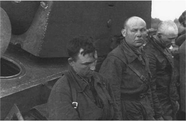 Танкисты из экипажа КВ-1 танкового батальона ВАММ, захваченные немцами в бою 2 июля 1941 года в районе Дагды. Обратите внимание на командира на переднем плане — на петлице под комбинезоном видна танковая эмблема и одна «шпала», соответствующая званию капитан. Второй, смотрящий в сторону, скорее всего, тоже командир так как у него командирский ремень.