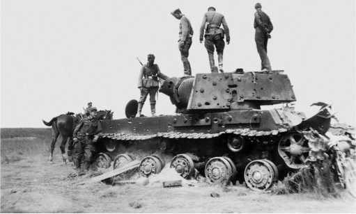 Подбитый танк КВ-1 выпуска июня 1941 года (опорные катки без усиления) из состава 21 — го мехкорпуса. На броне машины видны многочисленные следы от снарядных попаданий, ствол орудия в откате — видна пробоина в бронировке противооткатных приспособлений (АСКМ).