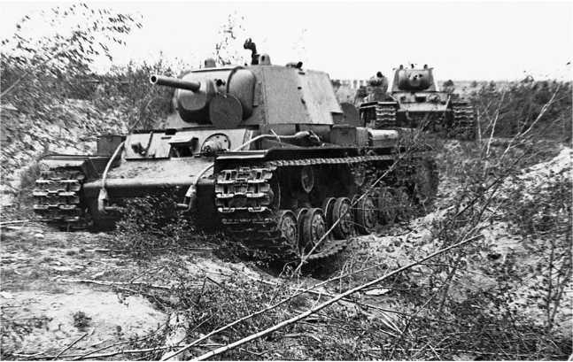 Танки КВ-1 выдвигаются на новую позицию. Ленинградский фронт, октябрь 1941 года. Передняя машина имеет упрощенную башню и дополнительные топливные баки (АСКМ).