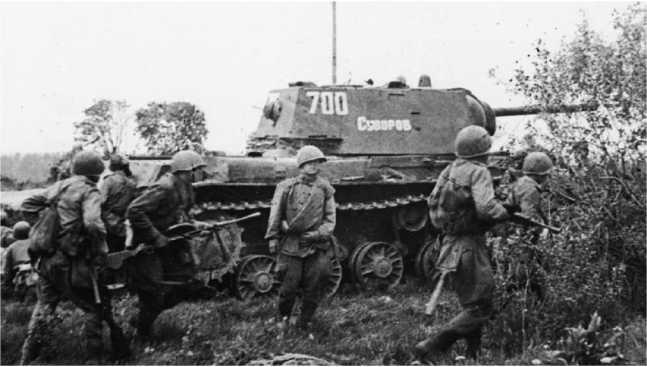 Автоматчики при поддержке танков движутся вперед. Ленинградский фронт, июнь 1944 года. Скорее всего, танк КВ-1 «Суворов» с номером 700, изображенный на снимке — машина командира 31-го гвардейского тяжелого танкового полка (РГАКФД СПБ).