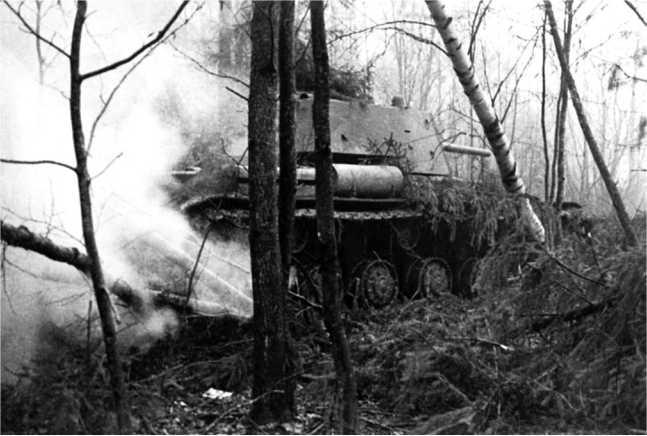 Танк КВ-1 движется по лесу. Октябрь 1941 года. Машина оснащена дополнительными топливными баками, на борту башни видны три снарядных отметины (ЦМВС).