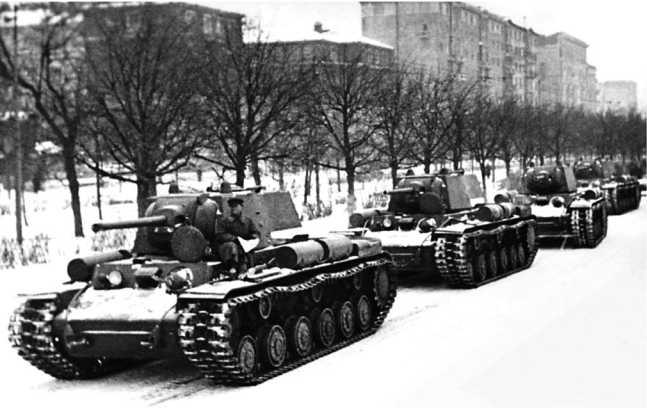 Колонна танков КВ-1 на улице Москвы. Декабрь 1941 года. Машины оснащены усиленными катками с внутренней амортизацией и дополнительными топливными баками (АСКМ).