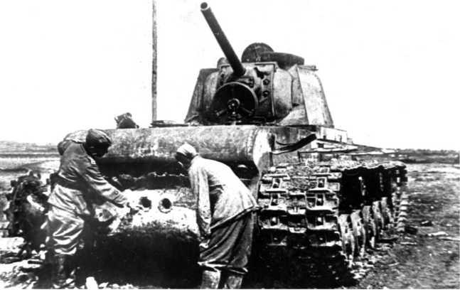Немецкие солдаты осматривают подбитый танк КВ-1 одной из частей Крымского фронта. Май 1942 года. Обратите внимание на две пробоины в нижнем кормовом листе корпуса (ЯМ).
