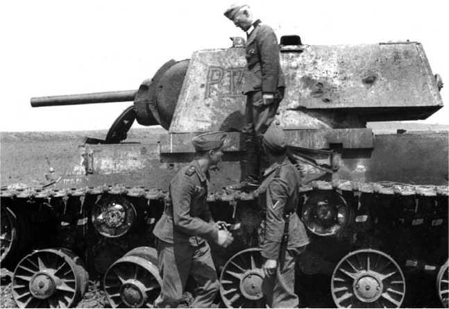 Немцы осматривают тот же танк КВ-1, что и на предыдущем фото. Хорошо видны следы многочисленных снарядных попаданий в корпус и башню машины (ЯМ).