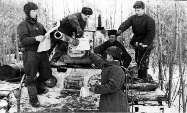 Раздача свежих газет в танковом подразделении. Калининский фронт, 1942 год. Машина оснащена дополнительными топливными баками (АСКМ).