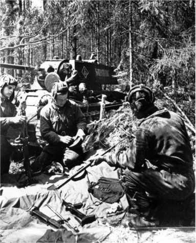 Старший сержант П. В. Костенко, старший лейтенант С. Г. Бандуровский и старший сержант И. С. Поляков проверяют пулеметы перед боем. 145-я танковая бригада, Западный фронт, 1942 год. На заднем плане КВ-1 «Багратион» (РГАКФД).