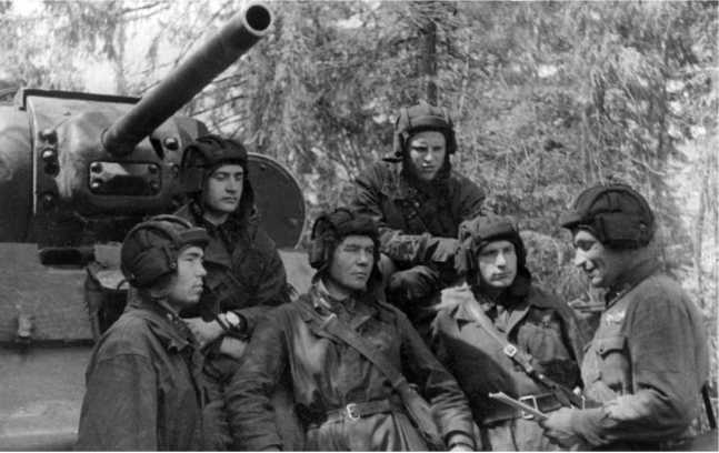 Комиссар подразделения старший политрук И. К. Худяков беседует с экипажем танка КВ-1. Северо-Западный фронт, 1942 год (РГАКФД).