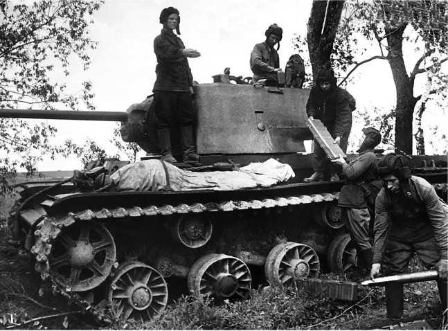 Экипаж КВ-1 лейтенанта С. И. Копченского пополняет боекомплект. <emphasis>1942 год. На фото хорошо видны чемоданы на два 76-мм выстрела, которые укладывались на пол боевого отделения танка (РГАКФД).