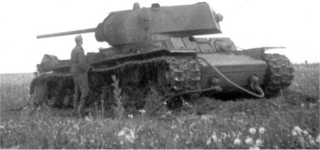 Немецкий солдат у подбитого танка КВ-1. Лето 1942 года. Судя по закрепленным буксирным тросам, машину пытались эвакуировать (АСКМ).