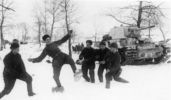 Танкисты развлекаются — опробуют трофейные немецкие боты из соломы. Декабрь 1942 года. На заднем плане — КВ-1 одной из танковых бригад (АСКМ).